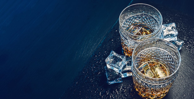 Dois caros copos de uísque com gelo em uma bandeja de pedra preta