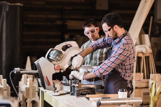Dois carpinteiros cortando a prancha de madeira com uma serra circular