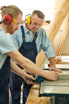 Dois carpinteiros cortando madeira