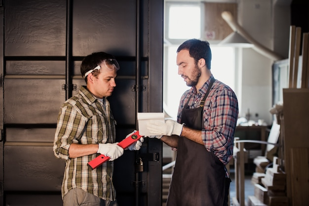 Dois carpinteiros estão conversando, segurando papéis e régua. um deles está usando máscara de segurança. carpintaria