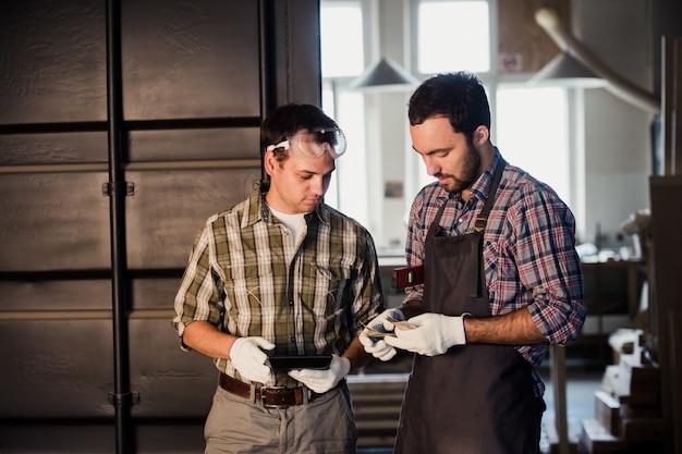Dois carpinteiros estão conversando, segurando papéis e régua. um deles está usando máscara de segurança. fundo de loja de carpintaria