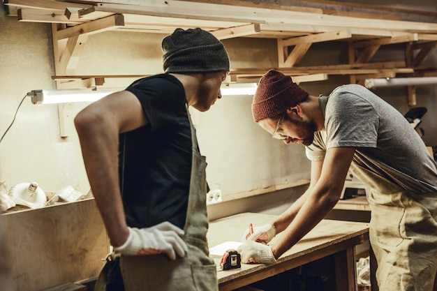 Dois carpinteiros fazendo esboços na bancada