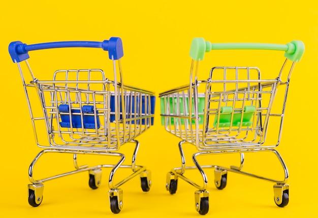 Dois carrinho de compras verde e azul em miniatura em fundo amarelo