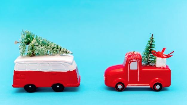 Dois carros de brinquedo vermelho e branco com árvores de natal. fundo azul
