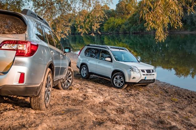 Dois carros estacionados na praia fluvial de outono. copie o espaço