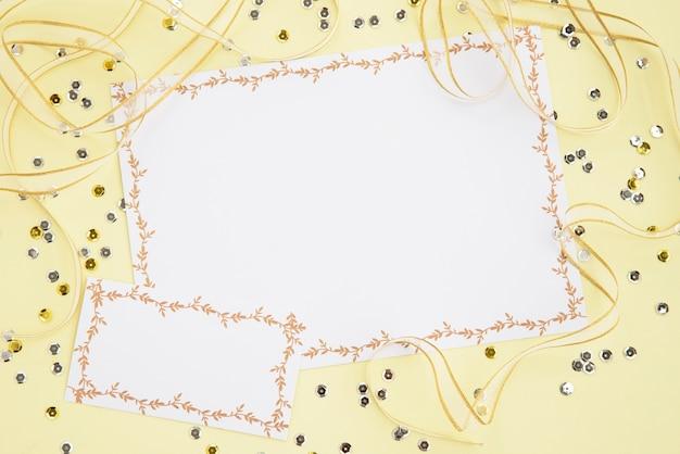 Dois cartões brancos em branco com lantejoulas e fitas na superfície amarela