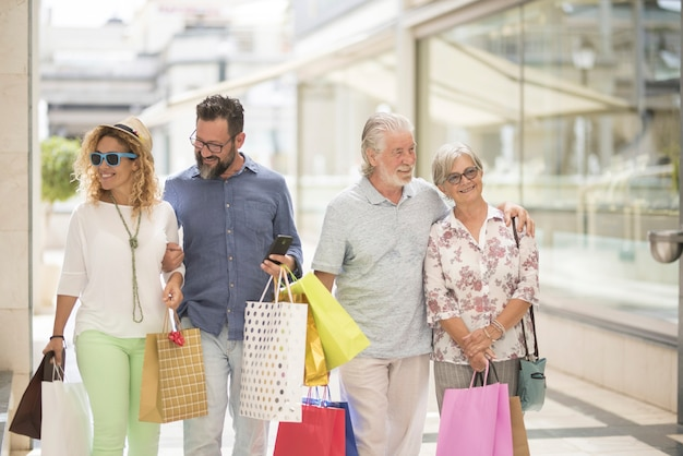 Dois casais de dois adultos e dois idosos vão às compras juntos no shopping com muitas sacolas com roupas e muito mais nas mãos - quatro pessoas felizes curtindo