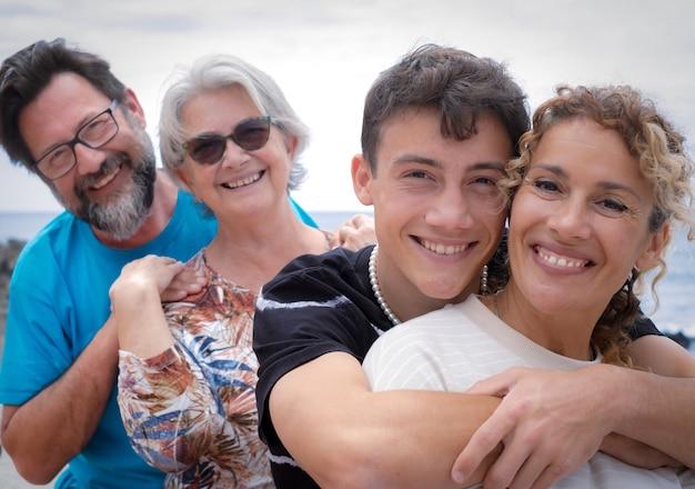 Dois casais de mãe e filho de diferentes gerações se abraçando e sorrindo ao ar livre