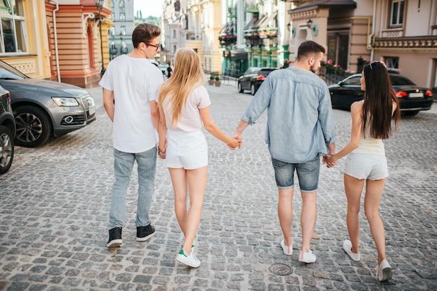 Dois casais estão caminhando juntos na rua