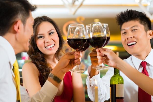 Dois casais ou amigos chineses asiáticos ou empresários brindando durante o jantar ou almoço em um restaurante elegante com taças de vinho tinto