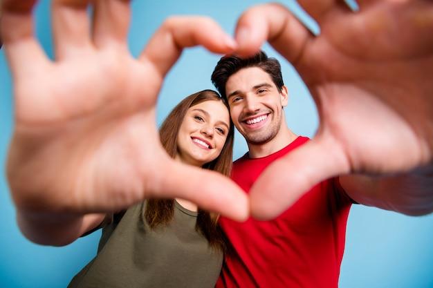 Dois casais românticos apaixonados e idílicos fazem as mãos do coração parecerem uma moldura, aproveite o dia dos namorados comemorando, use uma camiseta vermelha verde isolada sobre um fundo de cor azul