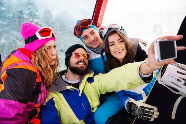 Dois casais se divertindo e praticando snowboard