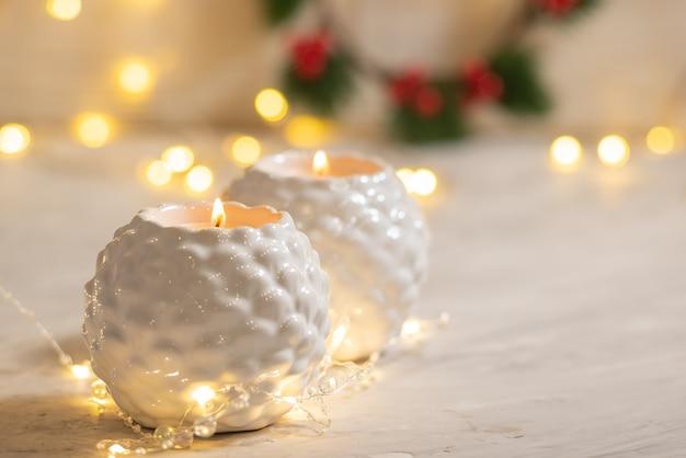 Dois castiçais brancos com chamas de canelas acesas e luzes guirlandas