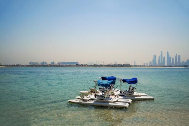 Dois catamarãs na água no fundo da cidade de dubai.