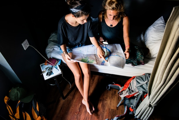 Dois, caucasiano, turistas, sentar-se cama, olhar, a, mapa