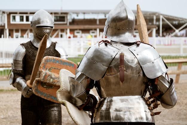 Dois cavaleiros medievais em armaduras pesadas prontos para lutar na batalha de reconstituição