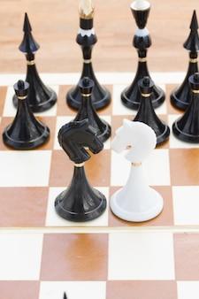 Dois cavaleiros preto e branco na frente do xadrez preto