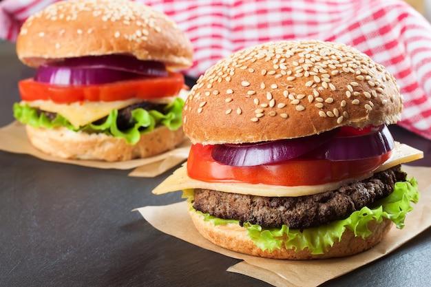 Dois cheeseburgers caseiros com hambúrgueres de carne e salada fresca em pãezinhos de marinhas, servidos em tabuleiro de ardósia preta.