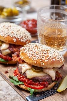 Dois cheeseburgers em pãezinhos de gergelim com jalapeño em mesa rústica de madeira