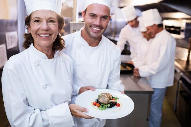 Dois chefs apresentando seus pratos