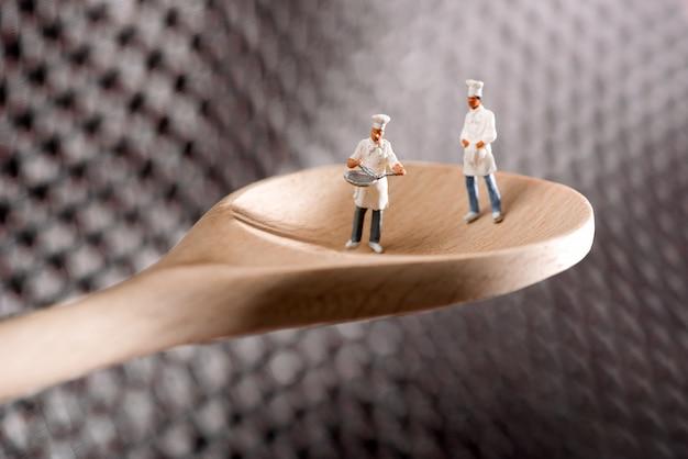 Dois chefs em miniatura ou cozinheiros em uma colher de pau
