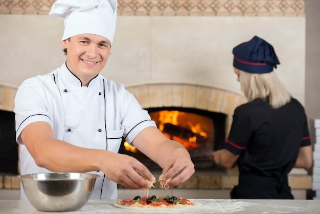 Dois chefs, homem e mulher estão no trabalho em uma pizzaria.