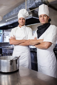 Dois chefs masculinos em pé com os braços cruzados na cozinha
