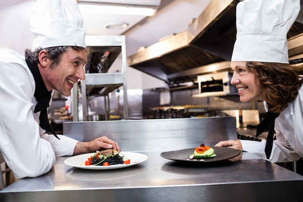 Dois chefs sorridentes, apoiando-se no balcão com pratos