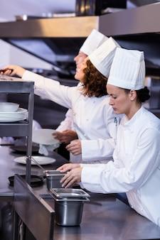 Dois chefs trabalhando na estação de pedidos em uma cozinha