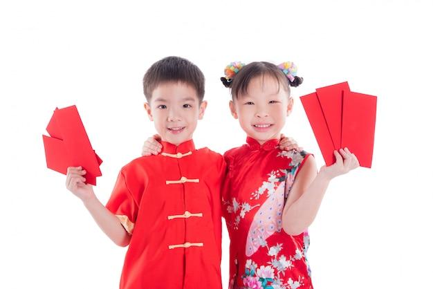 Dois, chinês, crianças, em, traje tradicional, segurando, dinheiro pacote vermelho, e, sorrizo