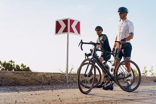 Dois ciclistas do sexo masculino param na estrada e descansam