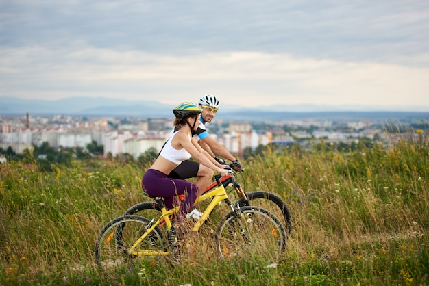 Dois ciclistas energéticos em capacetes andando de bicicleta na grama alta.