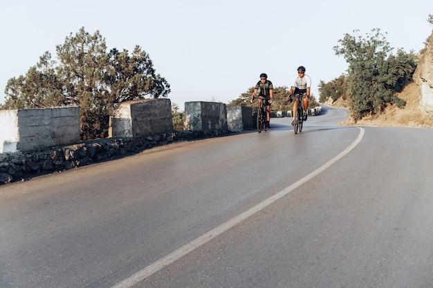 Dois ciclistas profissionais do sexo masculino andando juntos em suas bicicletas de corrida pela manhã na estrada costeira