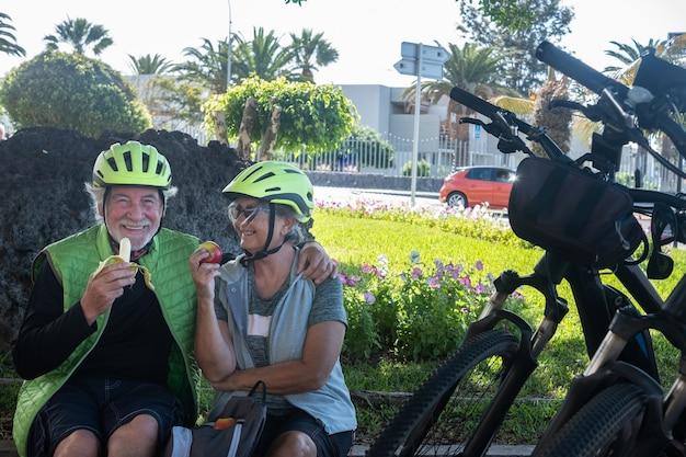 Dois ciclistas seniores com capacete amarelo fazem uma pausa em um parque verde comendo uma fruta e sorrindo. momento de relaxamento com as bicicletas perto deles