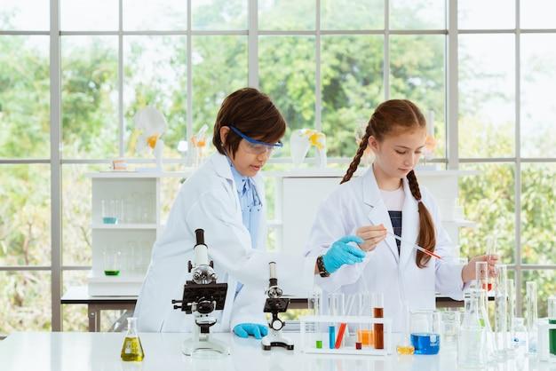 Dois cientistas das crianças que fazem experiências químicas com vista do microscópio na sala do laboratório.