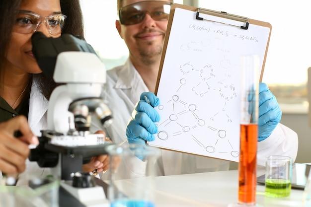 Dois cientistas de um estudante químico estão conduzindo