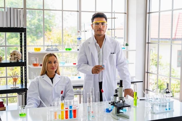 Dois cientistas estão experimentando na sala de ciências