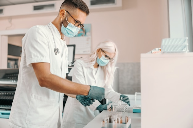 Dois cientistas focados com luvas de borracha e máscaras, segurando tubos de ensaio com sangue e fazendo pesquisas para a cura do vírus corona.