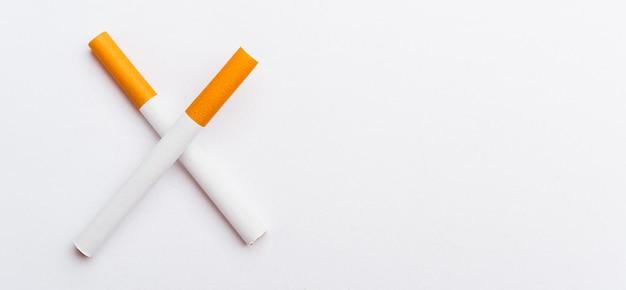 Dois cigarros cruzados barras fechem a pilha cheia de cigarro ou tabaco