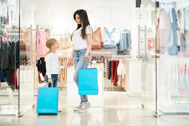 Dois clientes bonitos segurando sacolas posando na loja.