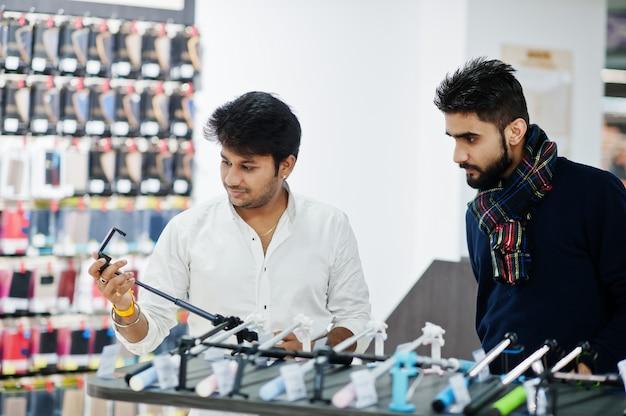 Dois clientes indianos na loja de telefonia móvel, escolhendo uma vara de selfie