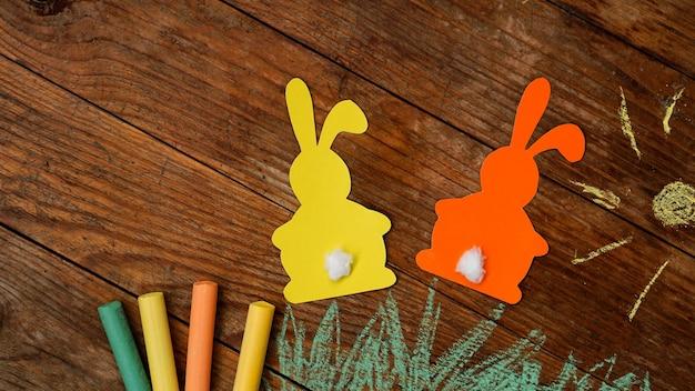 Dois coelhinhos da páscoa de papel. desenhado com grama de giz colorido e sol sobre uma superfície de madeira. desenho festivo com giz de cera.