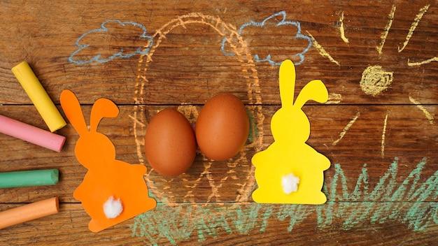 Dois coelhinhos da páscoa feitos de papel e ovos em uma cesta. desenhado com grama de giz colorido e sol sobre uma superfície de madeira. desenho festivo com giz de cera.