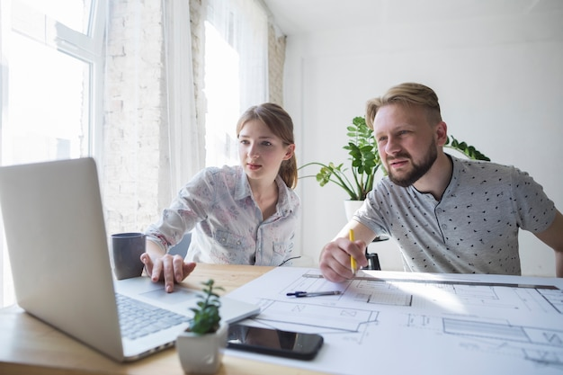 Dois, colega trabalho, olhar, laptop, enquanto, trabalhando, em, escritório