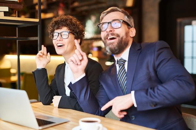 Dois colegas animados em trajes formais, sentado no café na frente do laptop, cantando e dançando pela mesa