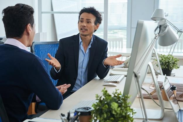 Dois colegas asiáticos discutindo no escritório