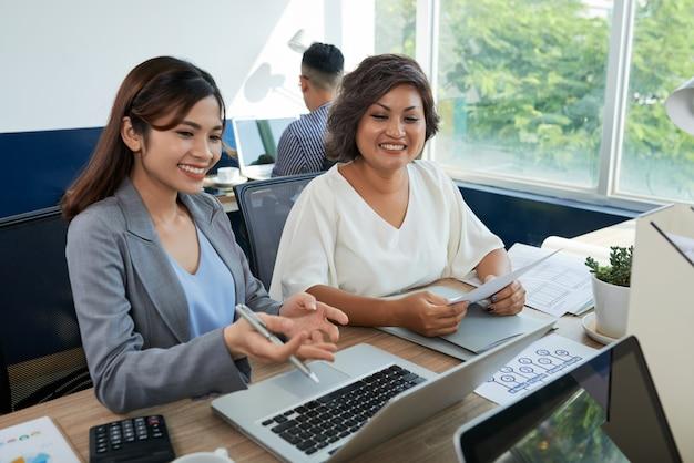 Dois colegas asiáticos estão sentados na mesa no escritório com laptop, uma mulher ajudando outra