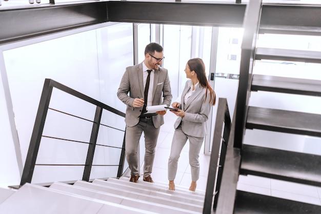 Dois colegas atraentes subindo as escadas e conversando. a comunicação entre os funcionários é um bom começo de um grande projeto.