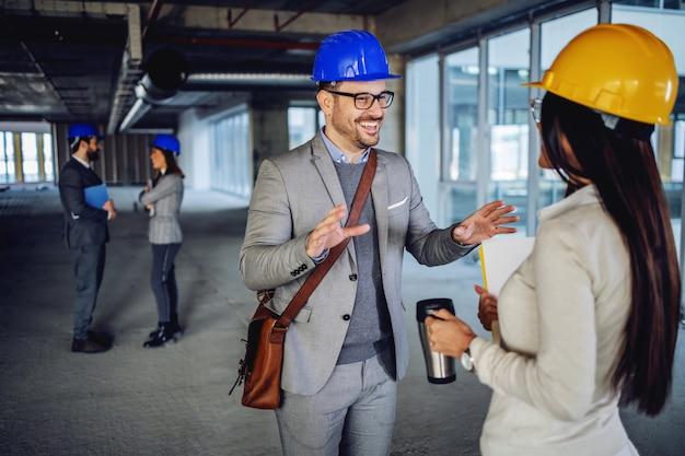 Dois colegas charmosos dentro do prédio em processo de construção, conversando e fazendo uma pausa do trabalho duro.