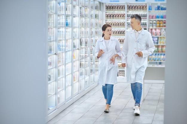 Dois colegas de jaleco branco andando pela farmácia